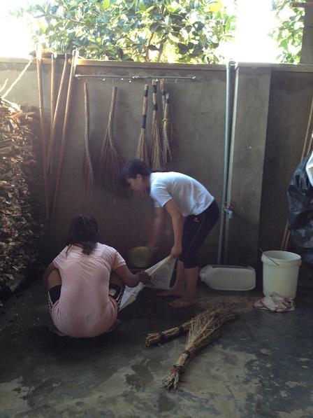 Em Razen và em Aidi giặt dụng cụ lao động sau khi đã làm xong.