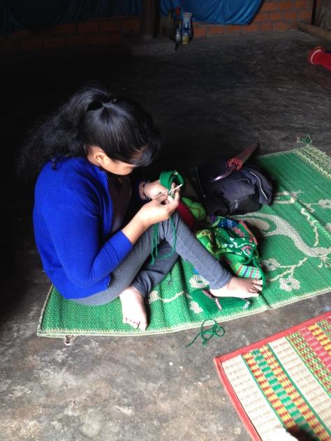 2/ Ảnh em Thuật ở thôn Tư liệt hai chân đang ngồi đan mũ và dớ em bé _ Buôn Hằng