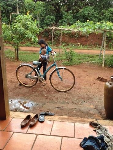 Em Ngân con bố mẹ Sriêng địu cháu đi xe đạp đến thăm bà ngoại Mai, ở Sóc Bù Ramang – Bù Đăng.
