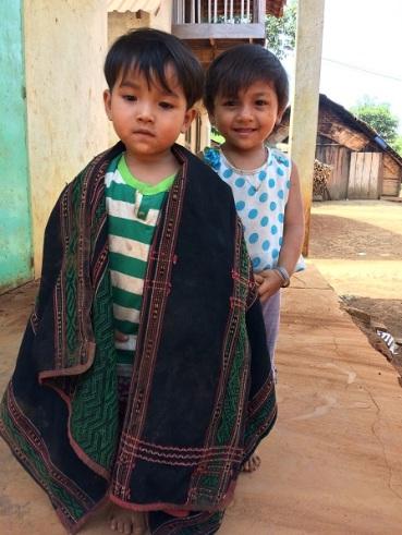 Hai em nhỏ ở sóc Bù Môn I đang chơi trước hiên nhà